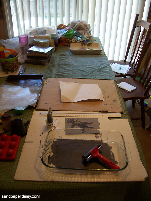 I cleared half my kitchen table and made different stations for each activity. From the foreground: 1) rolling ink onto the brayer, 2) inking up the plate, 3) pressing paper onto the plate and burnishing and 4) wetting the paper.