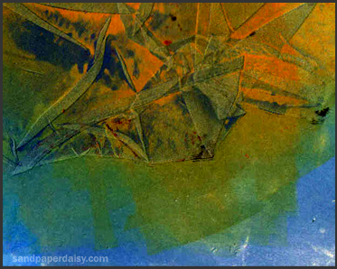 blue and orange abstract monoprint using embossed folds of satin to create a form.