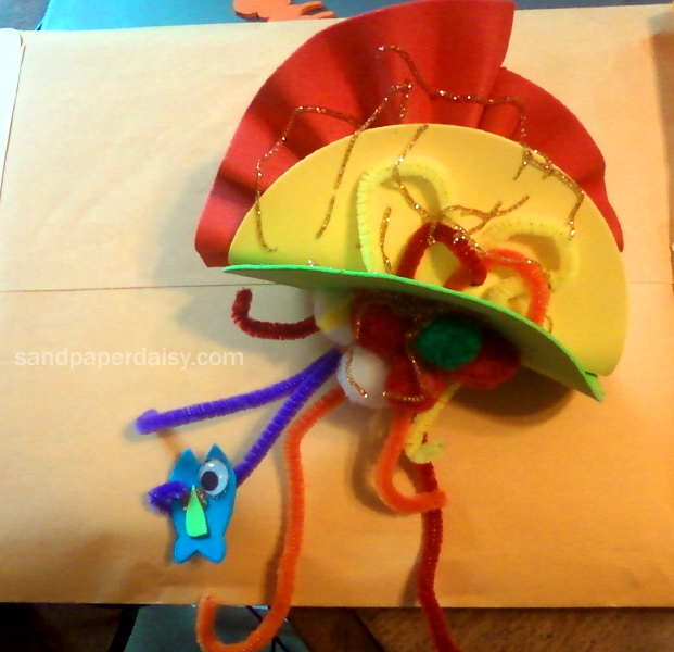 a foam and pipe cleaner jellyfish clutching a panicked little fish with googly eyes.
