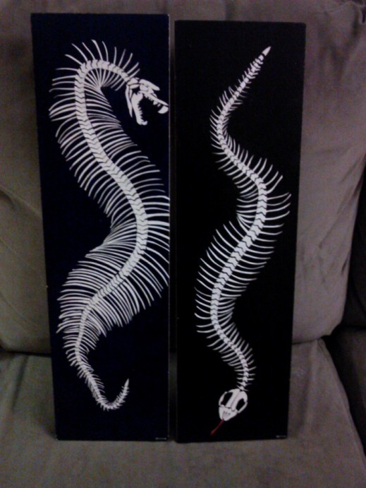 two snake skeletons created with paper decoupaged onto wood and acrylic