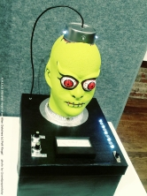 A sculpture showing a decapitated green hairless alien with red eyes and blinking lights on the top of its scalp by artist Patti Kiegel