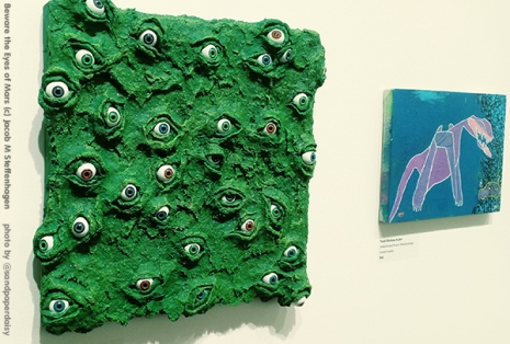 An emerald green knobby square piece of art protruding all over with bulging human eyes of all colors, in 3D. By artist Jacob M Steffenhagen.