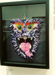 A mixed media depiction of a fanged and furry beast, at once whimsical and scary, somewhat resembling a monkey or baboon. By artist Brittany Scheller.