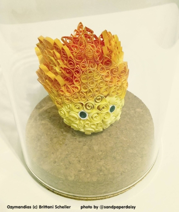 A small anime style flame reminiscent of the demon from Howls Moving Castle composed of tightly wound scrolls of colored paper by artist Brittani Scheller