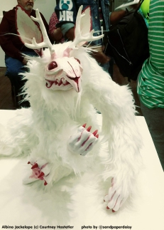 A full body sculpture of a white furred and red eyed bunny rabbit cryptid with antlers by artist Courtney Hostetler