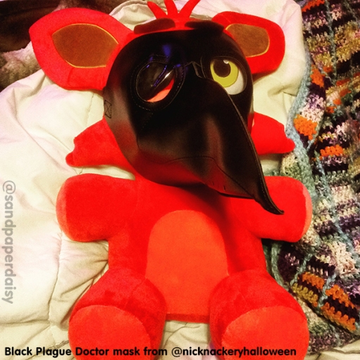 A black leather plague doctor mask avalilable from Nick Nackery Place in Evansville, Indiana, aka NickNackeryHalloween, being modelled on a giant Foxy the Pirate doll from five nights at freddys