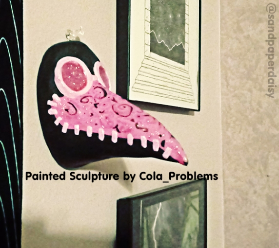A pink and black magical girl style plague doctor mask sculpted of clay and painted by artist Cora Dean of Cola_Problems, shown here in profile