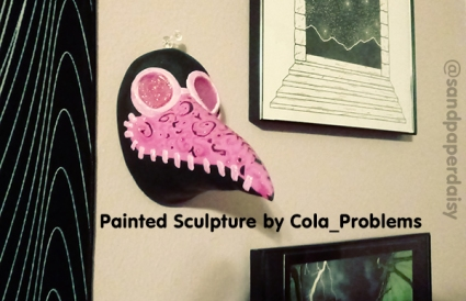 A pink and black magical girl style plague doctor mask sculpted of clay and painted by artist Cora Dean of Cola_Problems