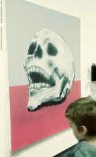 A large pastel and charcoal depiction of a grinning human skull by artist Jonathan Hittner.
