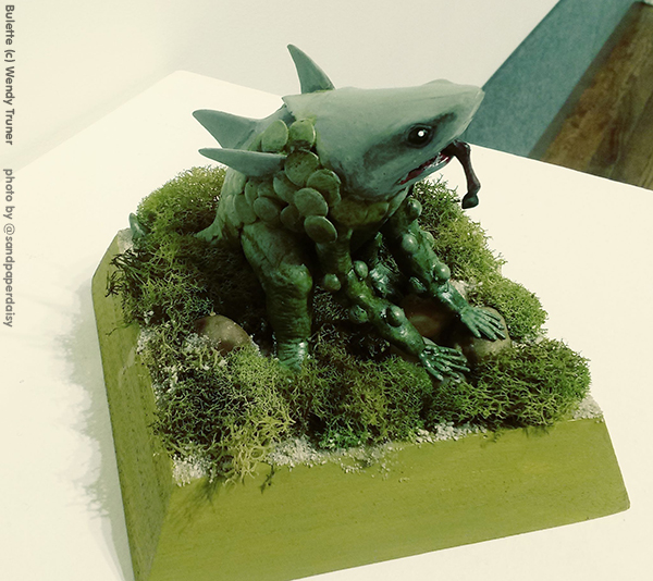 A small sculpture of a bipedal mossy monster with the head of a great white shark by artist Wendy Turner