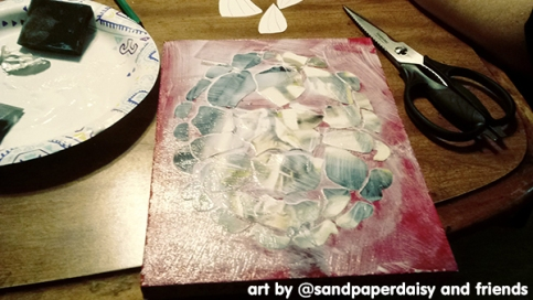 A decoupage box turtle in progress consisting of colored paper glued to wood in a turtle shell pattern