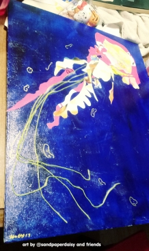 A completed decoupage jellyfish consisting of paper and embroidery floss of delicate pinks on a canvas board painted deep blue accented with bubbles in gold ink. It has since been sold