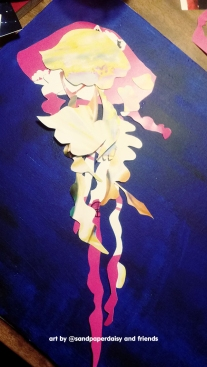 Colorful paper pieces laid for a decoupage jellyfish on a deep blue painted canvas board
