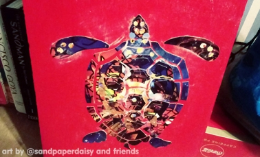 A completed decoupage of a sea turtle featuring deep blues and browns and accented with gold ink, glued onto a board painted scarlet.