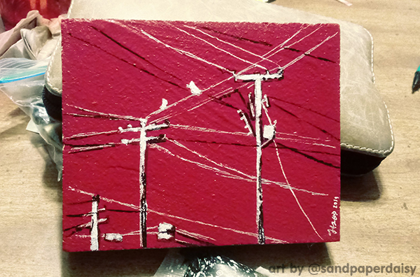 A very small painting on a thick square of wood, consisting of black and white ink telephone poles drawn onto a red paint base.