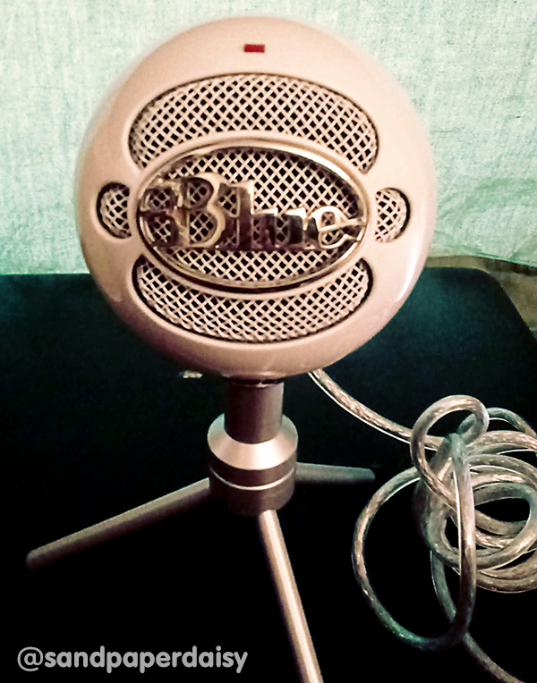 A photo of a Blue Snowball microphone, a ball shaped microphone mounted on a tripod used in podcasting and other endeavors